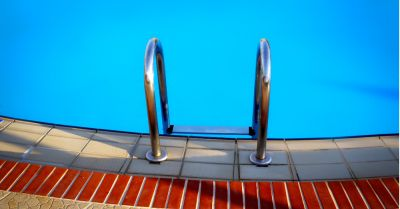 metal ladder leading into blue swimming pool water from a tile deck