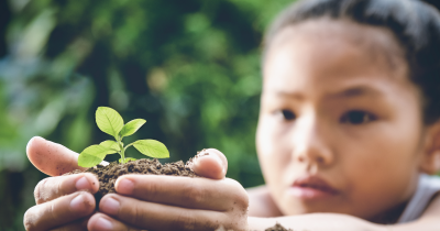 Girl planting a plant.