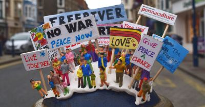 figures and toys arranged with signs protesting war and climate change