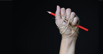 Hand with pencil wrapped in string.