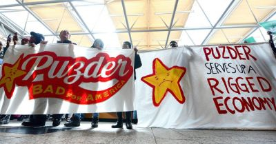 Fast food workers at a Fight for $15 protest against CEO Pudzer