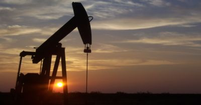 oil or fracking pumpjack drilling into the earth at sunset