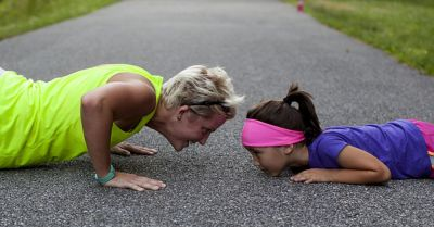 woman and child doing push ups and exercising