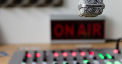 microphone and mixing board in front of an ON AIR sign in a radio studio