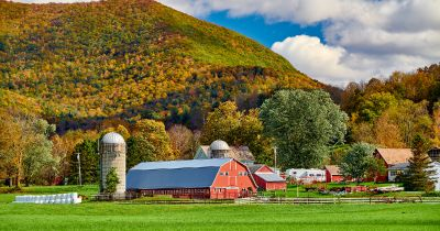 red barn and silo on a farm field beside a mountain landscape