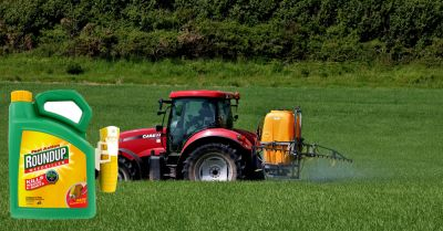 red farm tractor spraying an agricultural field with Monsantos Roundup herbicide