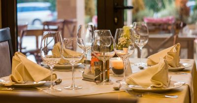 table in a restaurant set with dishes flat ware and wine glasses
