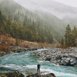 man standing near a river in a mountain valley landscape