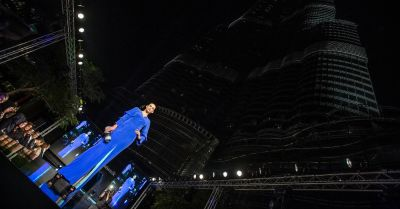 model walking a catwalk runway in front of a skyscraper at night during a fashion show