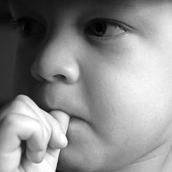 worried young boy chewing on his thumb fingernail