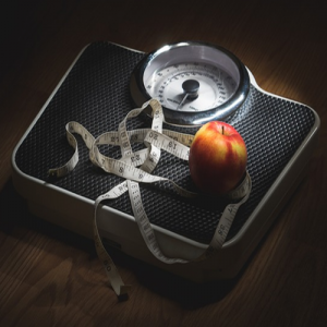 Measuring tape and an apple on a scale