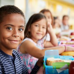children in a school cafeteria eating from lunch boxes
