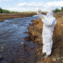 scientist in a hazmat suit testing a water sample from a river