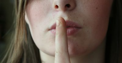person with finger over mouth indicating silence