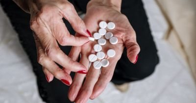 elderly person holding a handful of round white pills in their hands