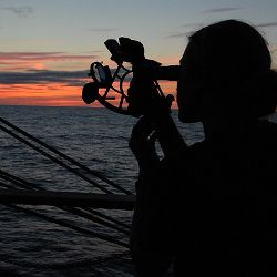 person navigating with a sextant on a ship in the ocean at sunset