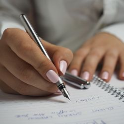 Woman writing in a notebook with a fountain pen