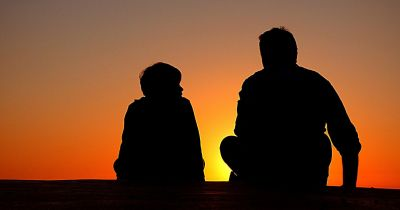 two silhouettes sitting in the sunset