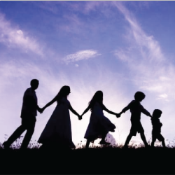 silhouette of a family walking in a line holding hands
