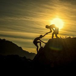 two people helping each other hiking up a mountain at sunset