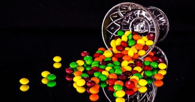Glass of candies spilling on to black background