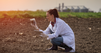 Soil being tested by woman in lab coat.