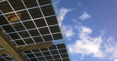 underside of a solar panel array against a sunny blue sky with white clouds