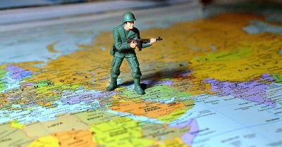 toy soldier resting between several countries on a map