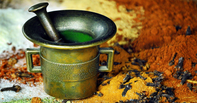 Mortar with piles of various spices laying next to it