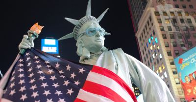 person dressed as the statue of liberty with the american flag on a city street