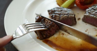 person cutting a steak on a white plate with a fork and knife