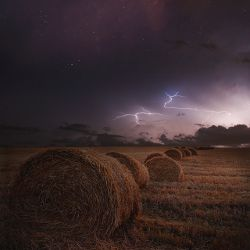 Lightning storm rising over hay bales on a farm field