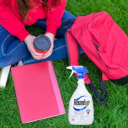 student on a campus lawn with books and a backpack as well as a bottle of Monsantos glyphosate herbicide ROUNDUP