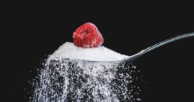 granulated sugar falling off a spoon with a raspberry on top