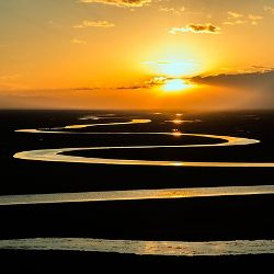 Winding and meandering river in the light of a sunrise on the prairie