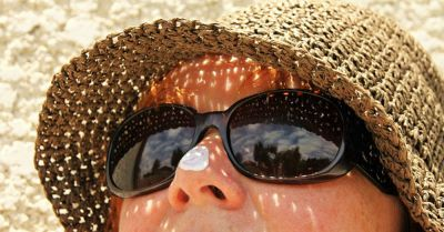 person with sunscreen on nose with hat and sunglasses on the beach
