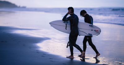Two surfers on the beach in wetsuits