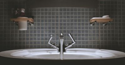 water faucet running in a tiled bathroom sink