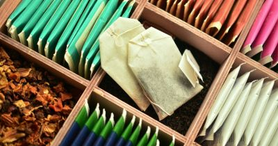 opened packages of tea bags sitting in a wooden container along with a section of loose leaf tea
