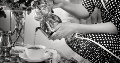 tea being poured out of a silver teapot in a black and white photo