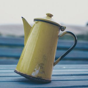 yellow metal teapot on a blue bench outside