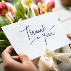 person holding a handwritten thank you card with a bouquet of pink flowers