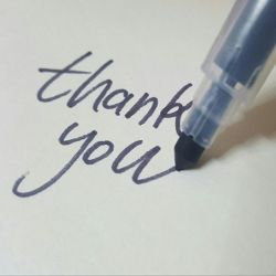 marker pen drawing the words Thank You on a white paper