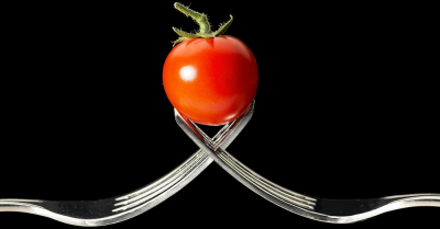 Two forks holding a tomato
