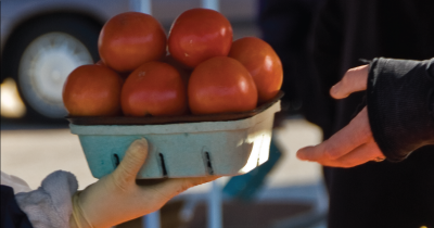 Someone buying tomatoes at a farmers market.