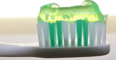 green plastic toothbrush with green toothpaste