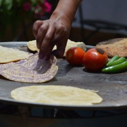 person making tortillas on a wood fire grill with tomatoes and peppers