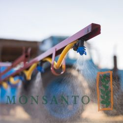 spray arm nozzle of a tractor on a farm field with the logo of MONSANTO