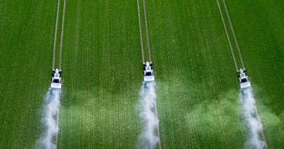 three tractors on a farm field spraying crops down with pesticides