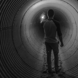 person walking down a large drain tunnel with a flare light